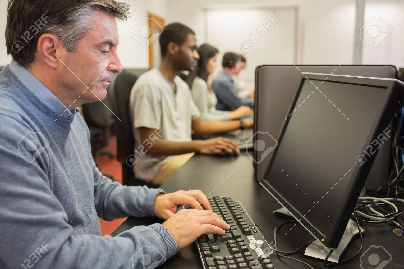 15584367-man-working-at-computer-in-computer-class-using